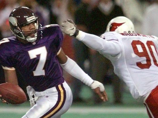 Minnesota Vikings quarterback Randall Cunningham scrambles out of the grasp of Arizona Cardinals' Andre Wadsworth, right.