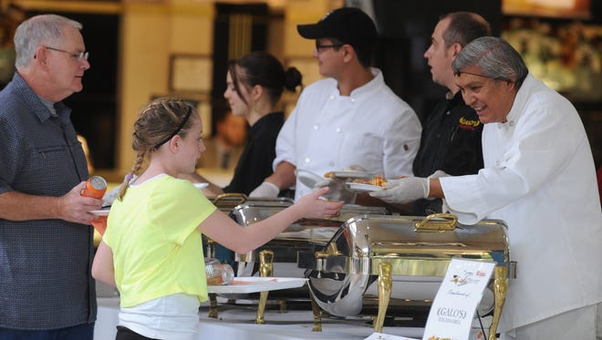 Ticketholders are served samples at the Galo's Italian Grill table during the Taste of Wayne County at Richmond Square Mall.