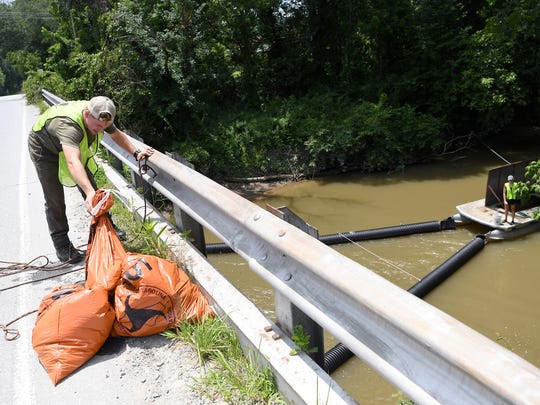 Jack Hendesron, with MountainTrue, hoists bags of trash onto the Balfour Road bridge over Mud Creek in Hendersonville as he works with members of Asheville GreenWorks to clean out their Trash Trout installed in the creek.
