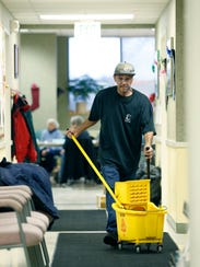 Larry Nobles, a janitor with Midnight Janitorial, cleans