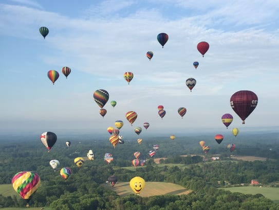 A mass ascension under blue skies during the balloon