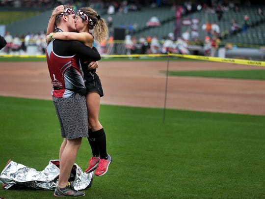 Halie Cottrill (right) embraces Tyler Kizzman after accepting his marriage proposal at the St. Jude Memphis Marathon finish line Saturday morning in Autozone Park.