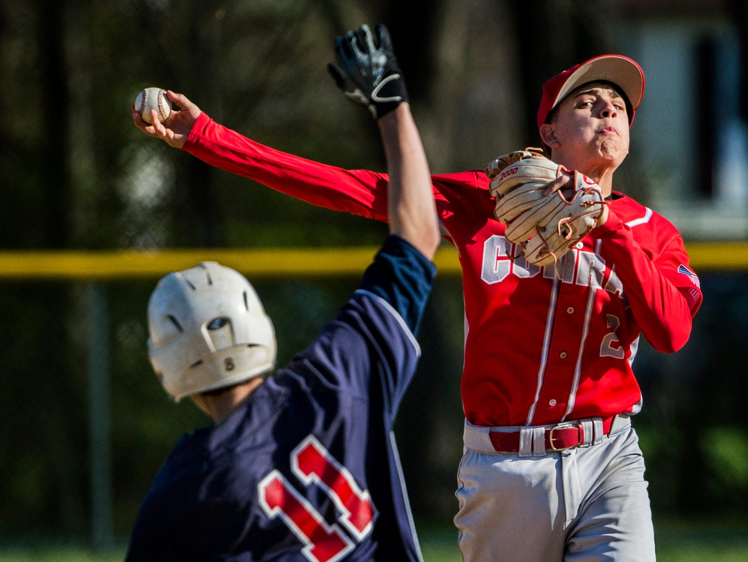 Conrad's Kevin Russo throws to first after tagging out Newark Charter's Ryan Walsh at second base as he turns a double play in Conrad's 11-0 win over Newark Charter on Wednesday afternoon.
