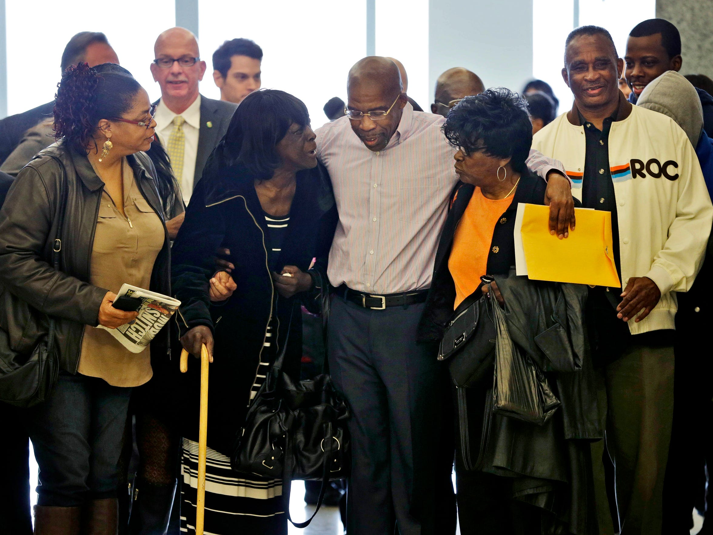 Jonathan Fleming, center, exits the courtroom with his mother Patricia Fleming, second from left, and other family and friends in New York on April 8, 2014. He spent almost a quarter-century behind bars for murder he didn't commit.
