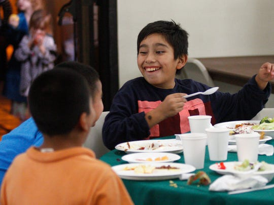 Abner Ramirez, 10, jokes while eating his meal as Many