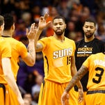 Phoenix Suns Marcus Morris and Markieff Morris (right) greet their teammates during a game against the Minnesota Timberwolves on Friday, Jan. 16, 2015 in Phoenix.