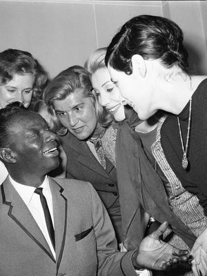 """Nat """"King"""" Cole before a recital at the Olympia Music Hall in Paris, surrounded by Parisian fans."""