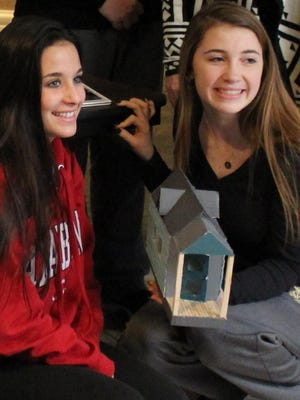 Designers Alexis McCarron, left, and Leighton Trimarco of St. E's Cre8tors team show that a tiny house model can be held in one hand.