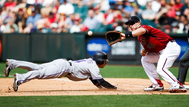 Colorado Rockies' Tony Wolters dives back to first base on a pickoff attempt as Arizona Diamondbacks' Paul Goldschmidt catches the on Sunday, May 1, 2016, at Chase field in Phoenix, Ariz.