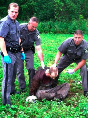 Police stand over David Sweat after he was shot and captured near the Canadian border on June 28, 2015, in Constable, N.Y.