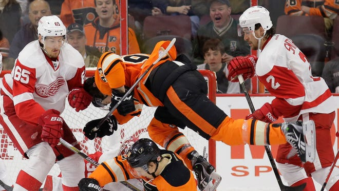 Flyers' Jakub Voracek (93) leaps over Brayden Schenn (10) as they battle for the puck with Detroit Red Wings' Brendan Smith (2) and Danny DeKeyser (65) during the third period Saturday in Philadelphia. Philadelphia won 7-2.