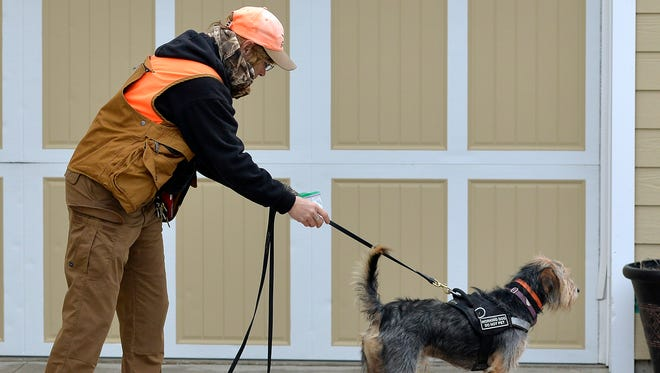 Lost Pet Professionals handler Angie Rutherford starts her dog, Oliver off Saturday, Dec. 12 with a scent at the garage where Angela Ausban's chocolate lab, Maggie, was last seen about a month ago in Sauk Rapids. Rutherford made the trip from rural Arkansas.