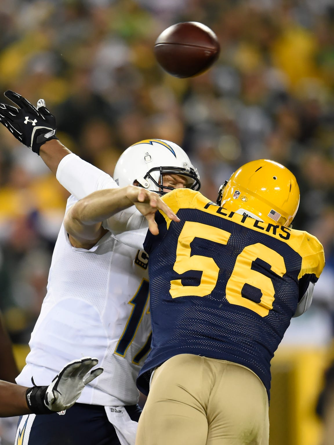 Green Bay Packers outside linebacker Julius Peppers (56) hits San Diego Chargers quarterback Philip Rivers (17) as he throws in the fourth quarter at Lambeau Field October 18, 2015.