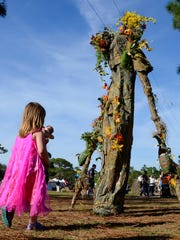Mallory Grimes, 5, checks out  the giant tree roaming the grounds on the first day of the Brevard Renaissance Fair in Wickham Park.