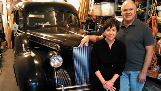 Cindy Geyer, shown with her husband Dick Kading and their 1940 Packard hearse, says she learned a respect for both life and death growing up and working in the family's funeral business in Albia.  She wore vintage mourning attire for this photo.