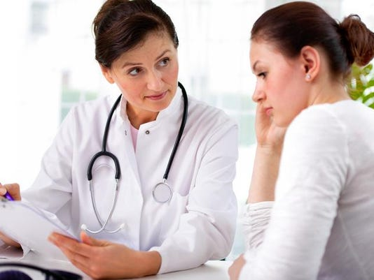 Female doctor and female patient looking over clipboard