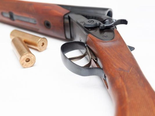 Opened double-barrelled hunting gun with bullets isolated on white