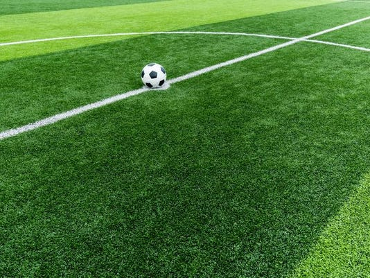 soccer field grass with ball at kick off point.