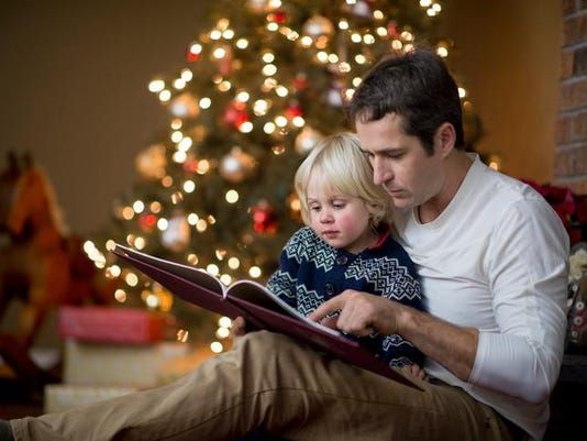 Father is reading his little boy a book on Christmas