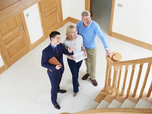 Realtor Showing Mature Couple Around House For Sale