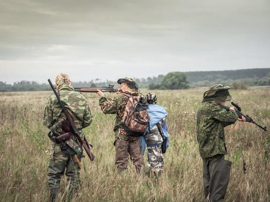 Hunters preparing for hunting in rural field in overcast day