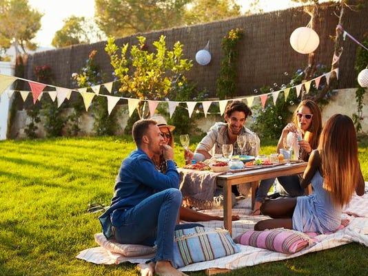 Group Of Friends Enjoying Outdoor Picnic In Garden