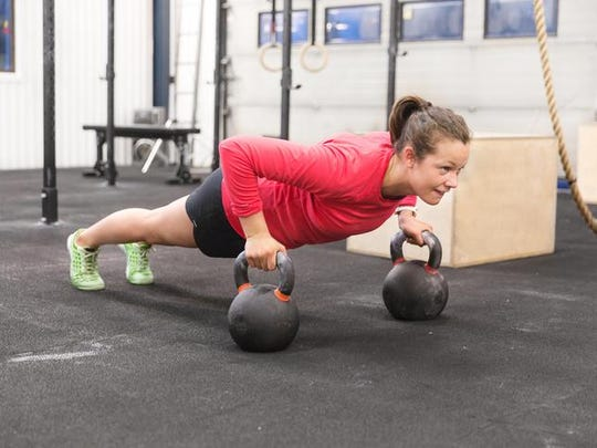 Young woman trains pushups with kettlebells