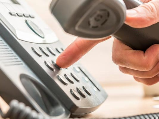 Closeup of male telemarketing salesperson holding a telephone re