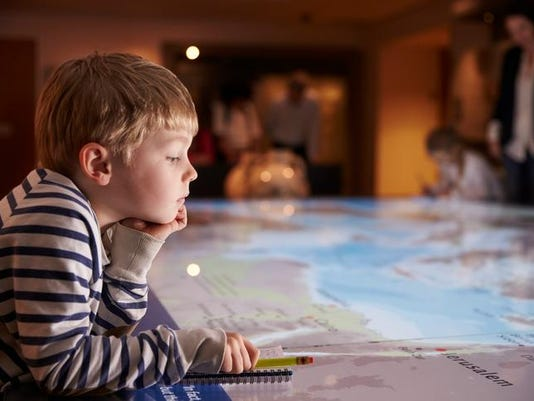 Boy On Trip To Museum Looking At Map And Writing In