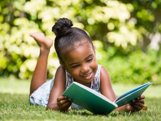 Little girl reading a book at park