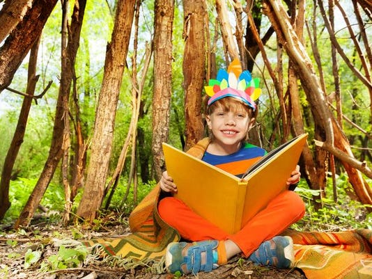 Cute smiling boy reading stories of Red Indians