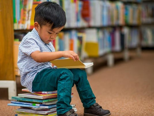 Little Boy Looking at Books