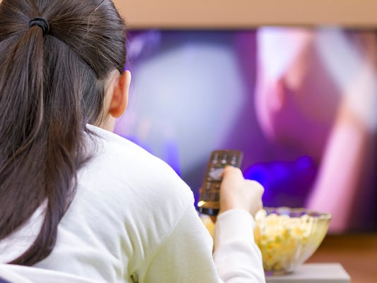 Relaxed teenage girl with remote control watching smart TV