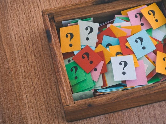 A wooden box filled with cards showing question marks.