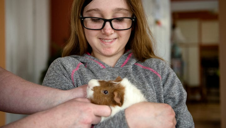 Layla Sands holds her guinea pig Moe while Layla's