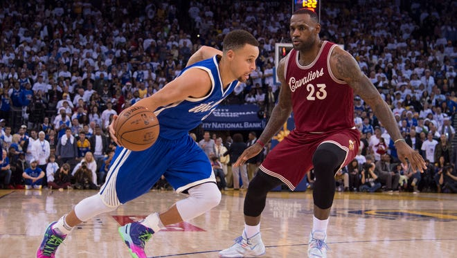 Golden State Warriors guard Stephen Curry dribbles the basketball against Cleveland Cavaliers forward LeBron James in the fourth quarter of a NBA basketball game on Christmas at Oracle Arena.