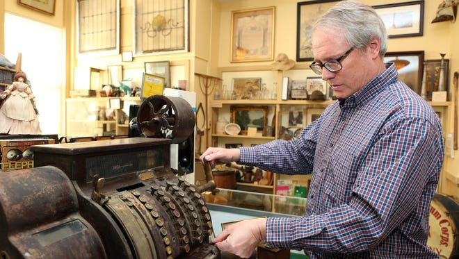 Suffern historian Craig Long tries the original cash register from The Green Room, March 21, 2016 at the Suffern Village Museum. The Hotel Lafayette, which housed The Green Room, was a banquet hall that hosted weddings and is being demolished for high-end apartment rentals.
