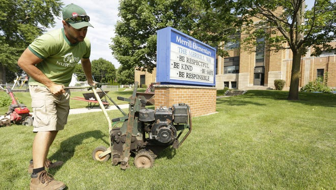Steve Heinzl, owner of Roe Nurseries, Inc., uses a turf cutter Thursday, Aug. 10, 2017, in order to make a flower bed in front of Merrill Elementary School in Oshkosh. Crews are getting ready for Project CURB, a beautification project for the Oshkosh Area School District, that will spruce up the schools' exterior.