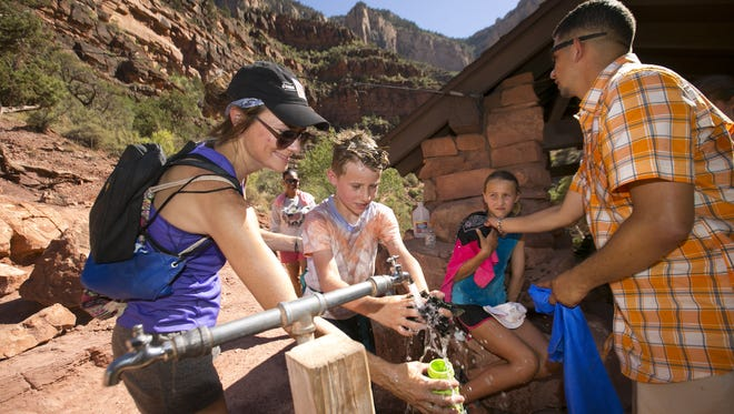 Lisa Fox (from left) of Kansas City, Mo., her son, Luke Fox, 9, her daughter, Emma Fox, 11, and Sean Arnold of Killeen, Tex., cool off with water from the Grand Canyon Trans-Canyon Pipeline, as the group hikes along the Bright Angel Trail above Indian Garden in Grand Canyon National Park on July 14, 2016. The Trans Canyon-Canyon Pipeline which was built between 1965 and 1970 brings water 15 miles from Roaring Springs below the North Rim all the way to the South Rim. The pipeline which is nearing 50 years old is continuously breaking making replacement necessary.