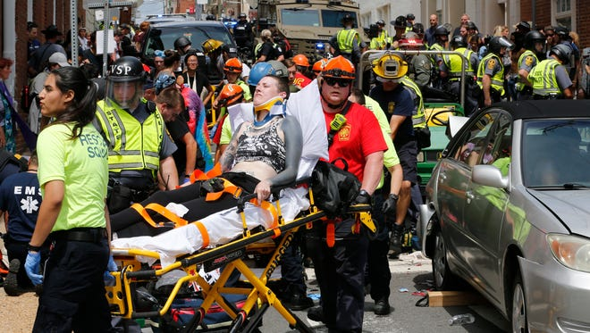 Rescue personnel help injured people after a car ran into a large group of protesters after a white nationalist rally in Charlottesville, Va., on Saturday. The nationalists were holding the rally to protest plans by the city of Charlottesville to remove a statue of Confederate Gen. Robert E. Lee. There were several hundred protesters marching in a long line when the car drove into a group of them.