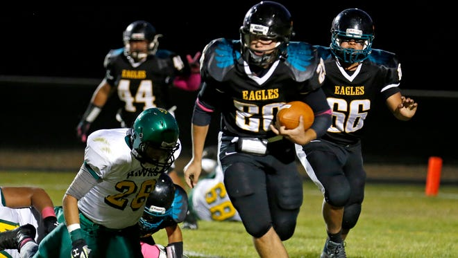 Navajo Prep's Jake Rogers breaks away from a tackle during a game against Thoreau on Oct. 2 at Eagle Stadium in Farmington.