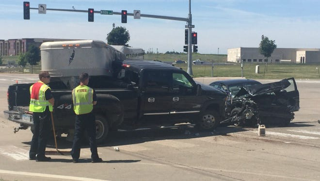Firefighters clean up the scene of a crash at 60th Street North and Marion Road on Friday.