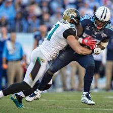 NASHVILLE, TN - NOVEMBER 10:  Chris Johnson #28 of the Tennessee Titans is tackled by Paul Posluszny #51 of the Jacksonville Jaguars at LP Field on November 10, 2013 in Nashville, Tennessee.  The Jaguars defeated the Titans 29-27.  (Photo by Wesley Hitt/Getty Images)