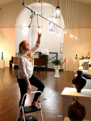 Amy Scroggins, the new Center For Art & Education curator, sets up the lighting, Tuesday, June 30, 2020, for the July 2, 2020, opening of the Earth, Wood, & Stone exhibit featuring artist Winston Taylor and Jason Davis in the Main Gallery. The opening reception will by 5:30 - 7 p.m. Thursday with the exhibition available by virtual tour at art-ed.org. The center is located at 104 N. 13th St. in Van Buren.