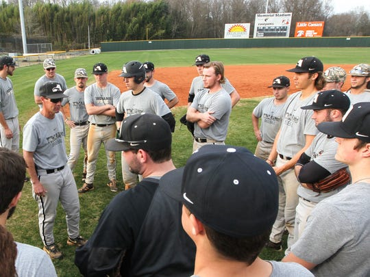 Joe Miller, left, Anderson University baseball coach, talks with players during a practice at Memorial Stadium. In the background, a new fence lines the outfield.