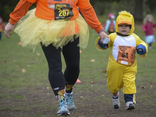 Caleb Gasparri, 2, runs in the kids quarter mile with his mother Jennifer Gasparri at the Pumpkins in the Park 5K in Cobbs Hill Park.