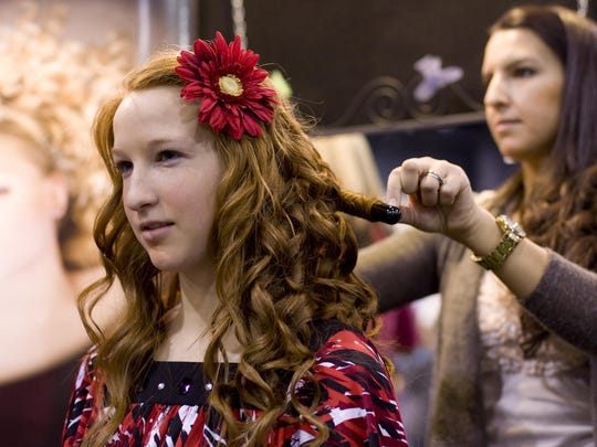 """Kylee Mills gets her hair curled at """"The Style You Want"""" booth during the 26th annual Santa's Workshop expo on Nov. 27, 2010."""