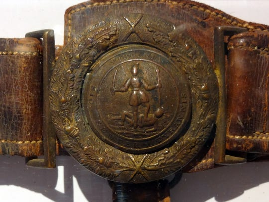 <137>Brice Stump photo. <137>The brass buckle on the belt worn by Henry A. Wise of Accomac shows wear after four years of military service. <137>The brass buckle<137> It features the Great Seal of Virginia. <137>Donated to the Eastern Shore Historical Society by the Wise family, it is now on permanent display at Ker Place in Onancock.<137>