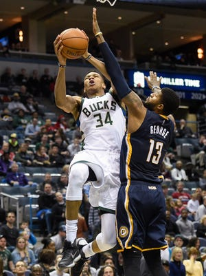 Giannis Antetokounmpo shoots against Pacers forward Paul George in the third quarter at the BMO Harris Bradley Center. The Bucks beat the Pacers, 99-85.