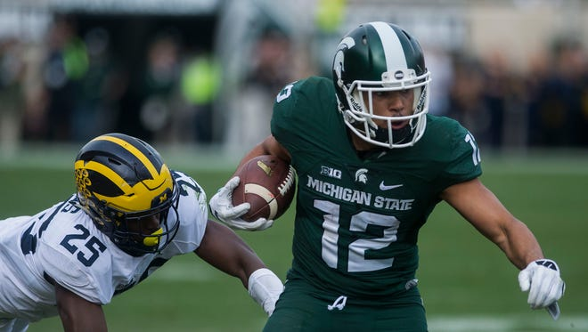 Michigan State Spartans WR R.J. Shelton is pursued by Michigan Wolverines' Dymonte Thomas during their game in East Lansing on Saturday, Oct. 29, 2016.